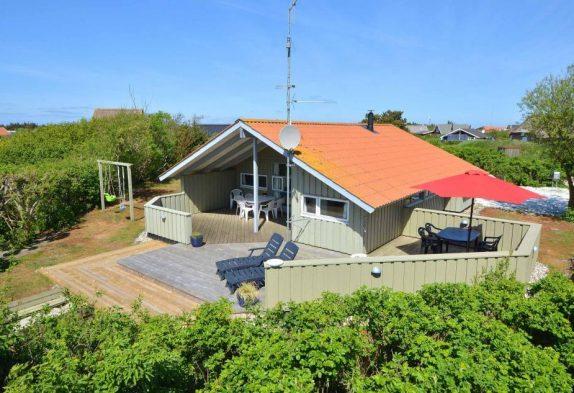 Haus mit Terrasse & Schaukel auf einem Rasengrundstück