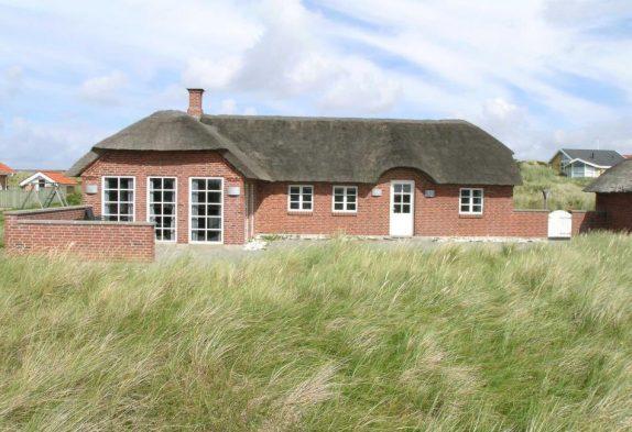 Ferienhaus mit Strohdach auf Naturgrundstück am Meer